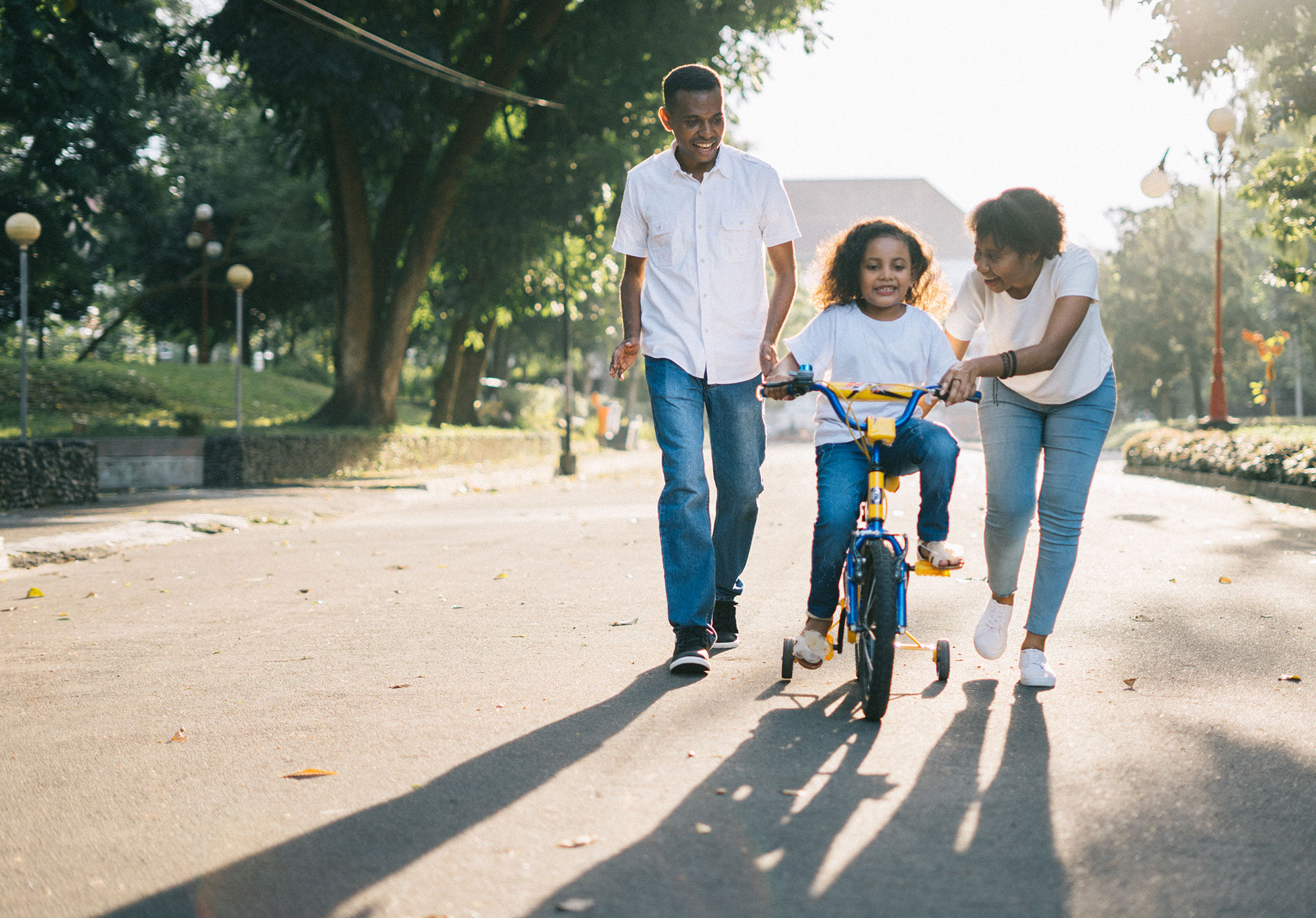 a child riding a bike with a father on one side and mother on the other, all three are wearing jeans and a white shirt